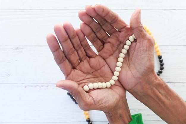 ラマダンで祈る年配の女性の手のクローズアップ