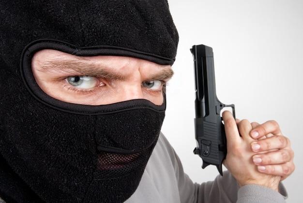 Крупный план серьезного вооруженного преступника с пистолетом