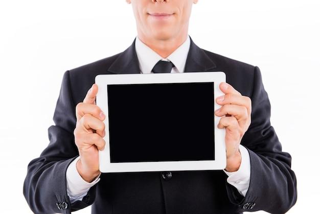 Крупным планом серьезный бизнесмен, демонстрирующий черный экран планшета