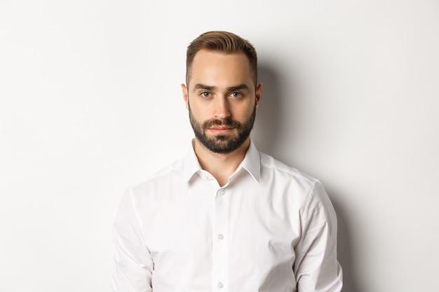 Крупный план серьезного бизнесмена в белой рубашке, смотрящего в камеру, уверенно стоя.