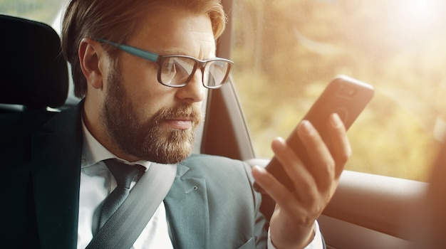 ロードトリップ中に車に座っているスマートフォンの画面を見ている真面目なビジネスマンのクローズアップ