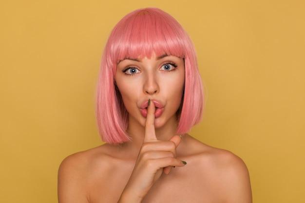 Крупный план серьезной молодой красивой женщины с короткими розовыми волосами, держащей указательный палец на рту, взволнованно смотрящей и просящей сохранить тайну, изолированной за горчичной стеной