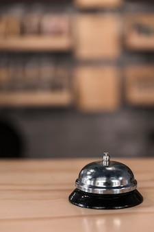 Close-up of service bell on wooden surface