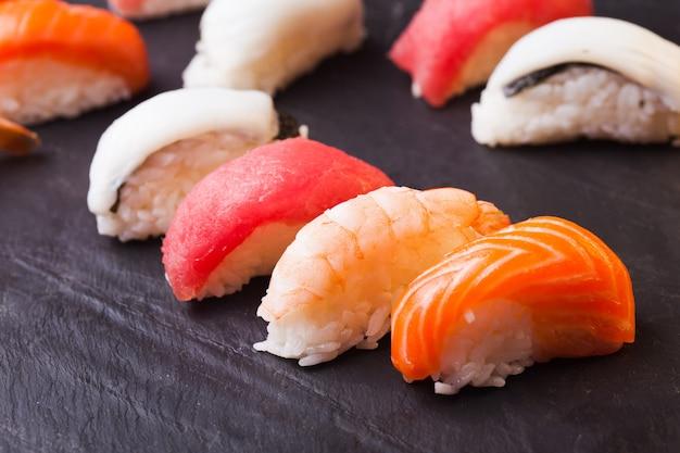 黒の背景に鮭、マグロ、ホタテ、エビの4つの寿司のセットのクローズアップ