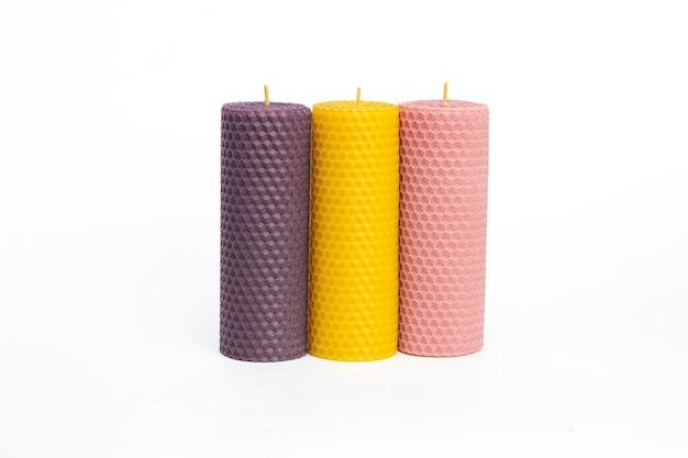 Закройте набор из трех фиолетовых, желтых и розовых декоративных свечей из натурального пчелиного воска с медовым ароматом для интерьера, изолированные на белом фоне