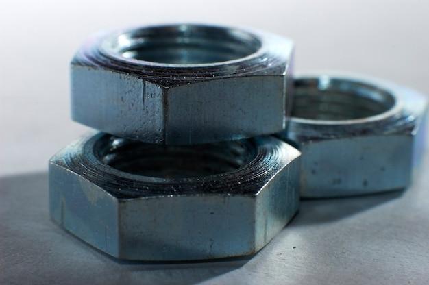 워크샵에서 금속 표면에 누워 여러 평면 금속 너트의 클로즈업.