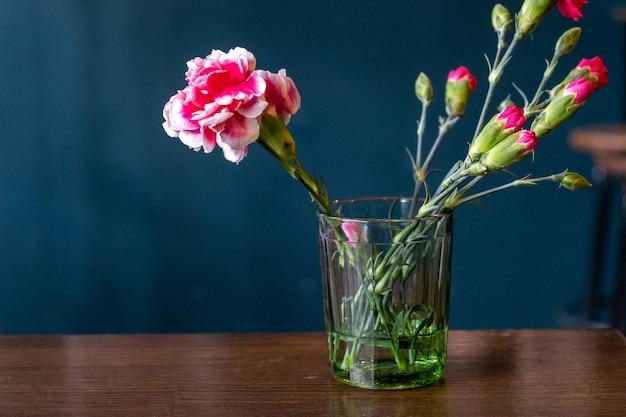 ガラスのいくつかのピンクのカーネーションのクローズアップ、選択的な焦点