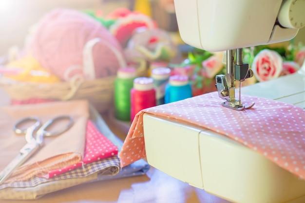 ピンクの布で働くミシンのクローズアップ