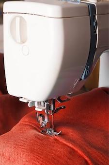 Закройте швейную машину, работающую с красной тканью