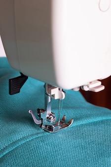 청록색 직물로 작업하는 재봉틀의 클로즈업
