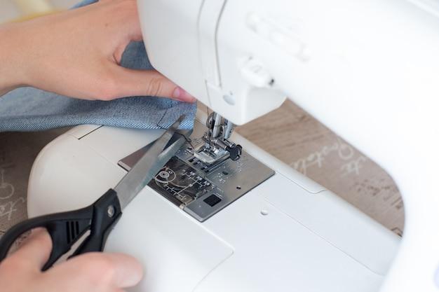 Крупный план шитья на швейной машине, рука с ножницами обрезает нить. концепция хобби, дизайна, самостоятельного создания эксклюзивных вещей.