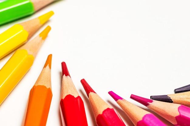Крупным планом острые цветные карандаши на белом фоне с копией пространства
