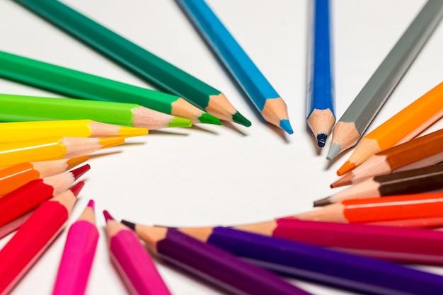 Крупным планом острые цветные карандаши на белом фоне
