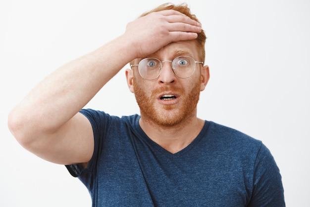ショックを受けた警戒された赤毛の男のクローズアップは額を叩いてパニックになり、何かを忘れました