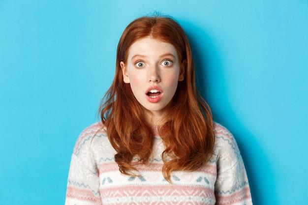 충격을 받은 빨간 머리 소녀의 클로즈업은 경외감에 턱을 떨어뜨리고, 파란색 배경에 서 있는 카메라를 놀라움으로 쳐다보고 있습니다.