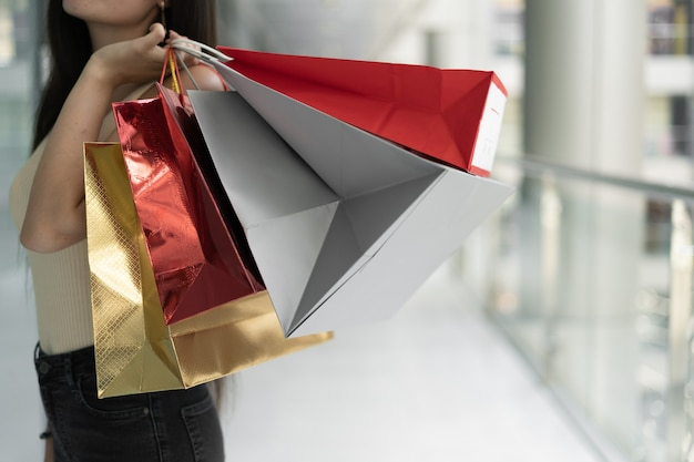 Крупный план хозяйственных сумок в женской руке, реклама покупок в модном магазине, женская рука держит красные и белые пакеты. торговый центр. копировать пространство,