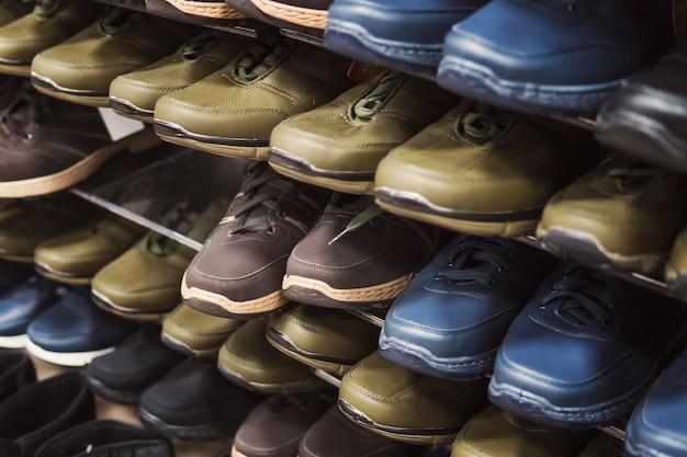 秋と春の予算にやさしいユニセックスの靴でショッピングスタンドのクローズアップ。靴市場のメンズスポーツシューズの棚。ジュニアシューズファッション。安い男性のブーツを買う。履物のペア。