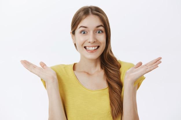 Крупный план пожимающей плечами невежественной девушки, улыбающейся, не подозревая