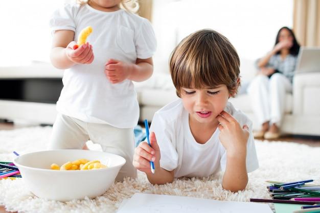 Крупный план братьев и сестер, которые едят чипсы и рисуют