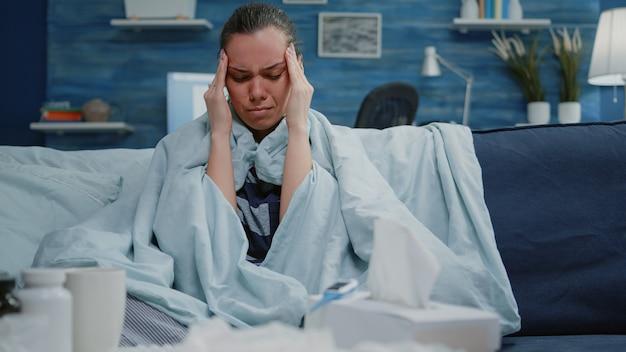 頭痛を治すためにこめかみをこすっている病気の人のクローズアップ