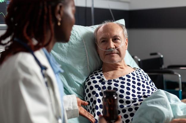 病院のベッドに横たわっている病気の体調不良の年配の男性患者のクローズアップは、医師の専門家の円盤投げを聞いています...
