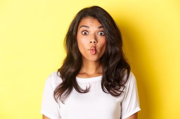 노란색 배경에 서서 입술을 빨고 놀란 표정을 하는 어리석고 재미있는 아프리카계 미국인 소녀의 클로즈업