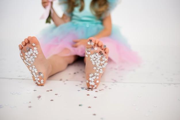축제 배경에 아이의 발에 은색 색종이 별의 클로즈업