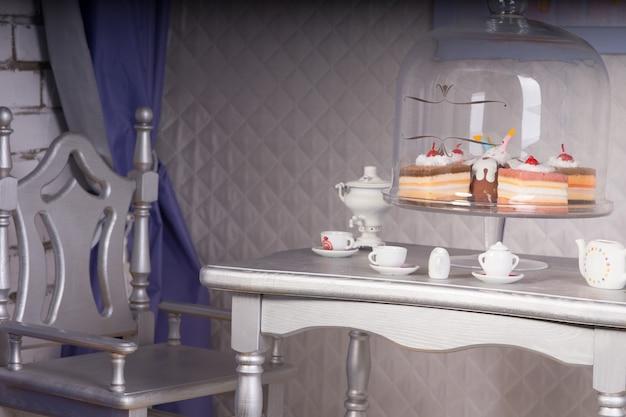 さまざまな退廃的なケーキとお茶のための銀のダイニングルームのテーブルセットのクローズアップ
