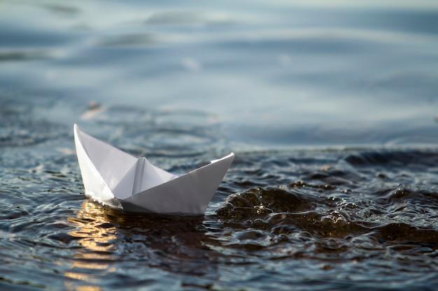明るい夏の空の下で青い澄んだ川や海の水に浮かぶシンプルな小さな白い折り紙紙の船のクローズアップ。自然の美しさ、自由、夢と空想のコンセプト。