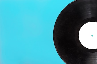 Close-up of single circular vinyl record on blue background