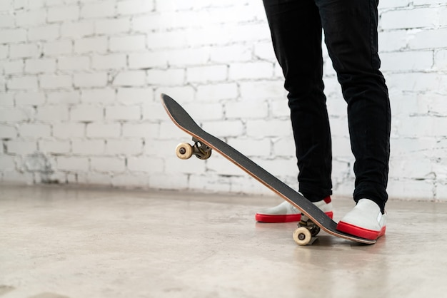 Закройте скейтбордиста, стоящего рядом с белой кирпичной стеной.