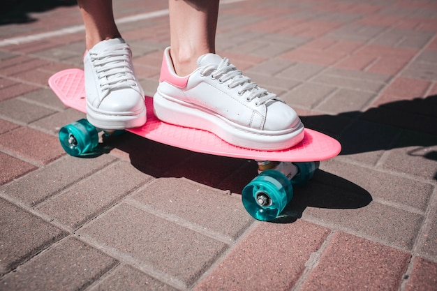 Крупным планом фигурист ноги и ноги носит белые кроссовки. девушка стоит на розовых коньках с обеих ног. на улице солнечный день.