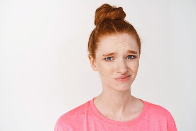 疑わしい、眉をひそめ、正面を見て不確かな、白い壁に立っている懐疑的な赤毛の女性のクローズアップ