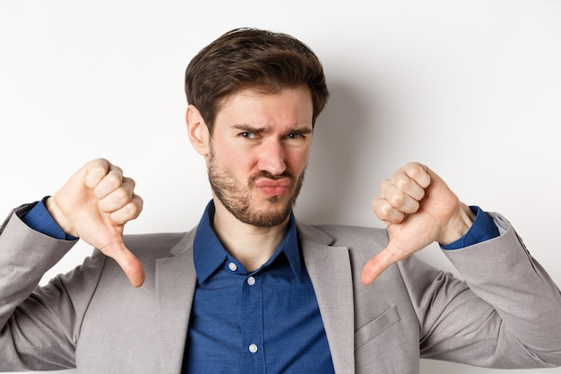 Закройте скептически настроенного молодого человека в костюме, показывая большие пальцы руки вниз, не любя и осуждая плохой продукт, отрицательные эмоции, белый фон.