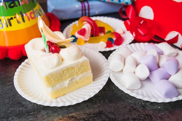 Крупный план кусочка торта; зефир и конфеты на бумажной тарелке
