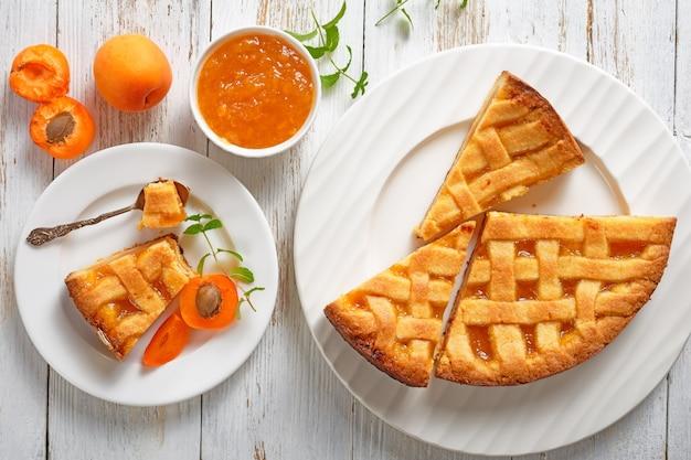 소박한 나무 테이블에 흰색 접시에 격자 파이 크러스트 토핑 슬라이스 살구 shortcrust 파이의 근접, 평면 평신도, 위에서 볼