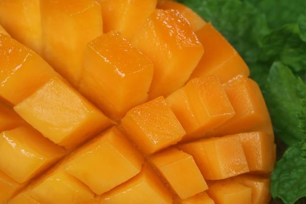Крупным планом нарезанный манго с зеленой мятой
