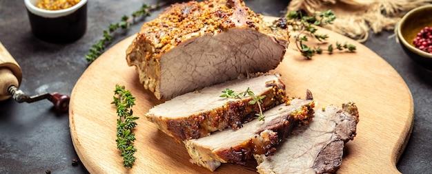 Крупный план нарезанной жареной свинины с тимьяном и горчицей на разделочной доске
