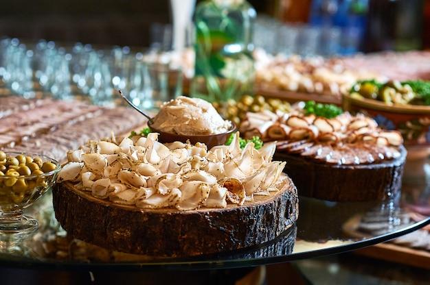 Крупным планом нарезанное острое сало на деревянной тарелке на столе в ресторане.