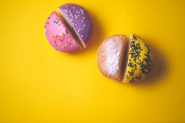 Крупный план нарезанных пончиков с начинкой, украшенных цветной глазурью на желтом бумажном фоне.