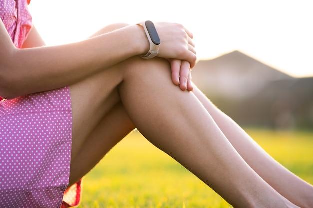 Закройте вверх стройных женских ног, отдыхая на лужайке зеленой травы в теплый летний день.