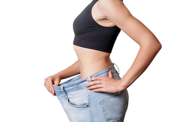 Крупный план тонкой талии молодой женщины в больших джинсах, показывающей успешную потерю веса, изолированную на белом фоне, концепцию диеты.