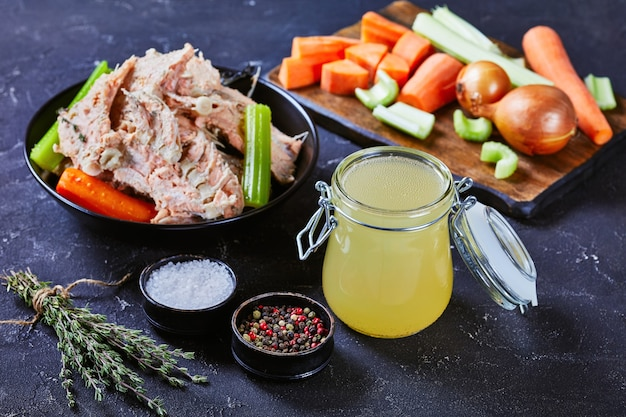 Крупный план медленно приготовленного рыбного бульона или бульона из лосося в стеклянной банке на бетонном столе с рыбным мясом, костями и овощами в миске