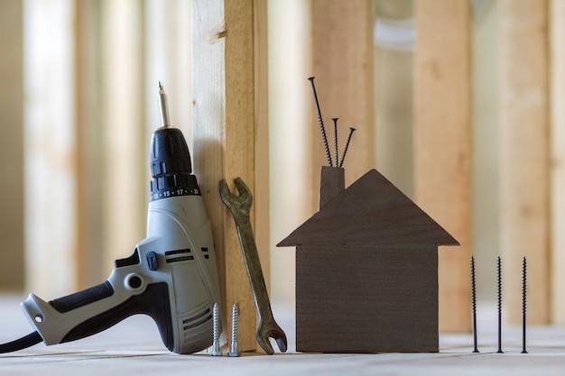 Конец-вверх малых коричневых модельных инструментов дома и здания на деревянных планках в незаконченной комнате под конструкцией. инвестиции в недвижимость, собственность и владение мечтой концепции дома.