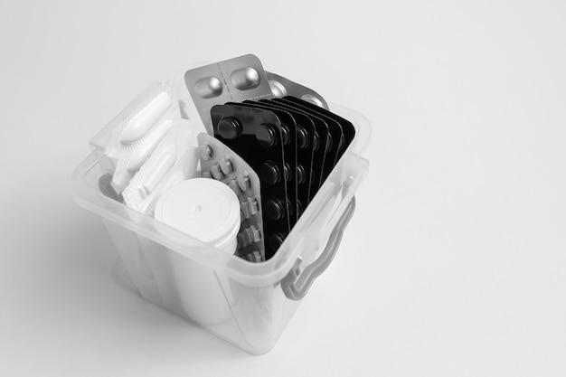 Крупный план небольшой аптечки с различными таблетками на белом фоне.