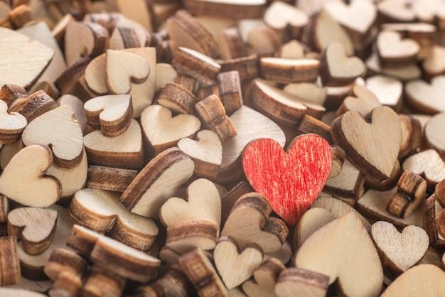 Крупный план маленького красного сердца в куче деревянного сердца