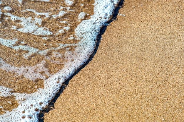 여름 맑은 해안에서 노란 모래 해변 위에 맑고 푸른 물으로 작은 바다 파도 닫습니다.