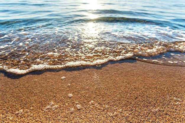 여름 햇살 가득한 해안의 노란 모래 해변 위에 맑고 푸른 물이 있는 작은 바다 파도를 닫습니다.