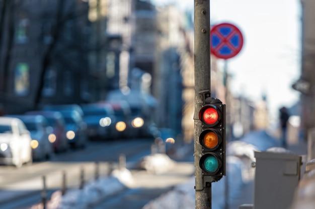 Крупный план небольшого дорожного семафора с красным светом на фоне городского движения