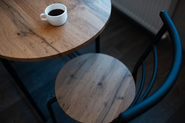 밝은 갈색 나무 책상에 에스프레소의 작은 흰색 컵의 클로즈업